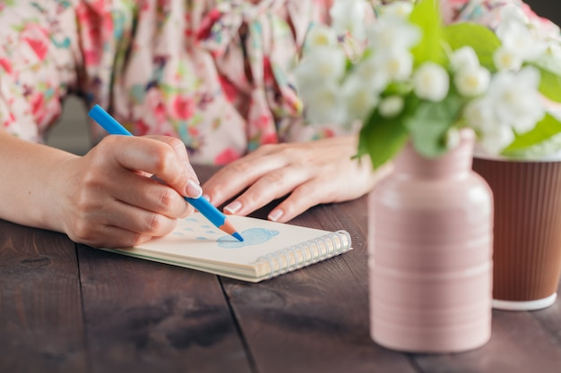 Woman drawing on notebook paper