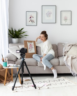 Woman drawing for an online tutorial indoors