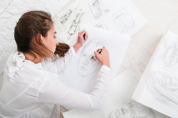 ワークショップで床に鉛筆の肖像画を描く女性