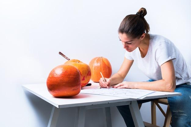 Женщина рисует эскизы персонажей тыквы