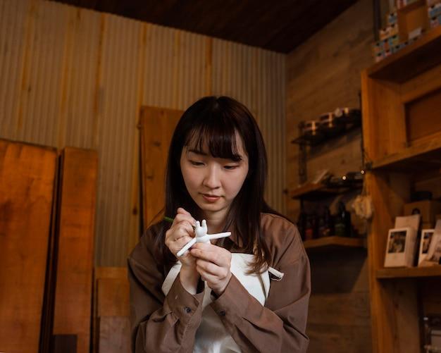 Женщина рисует статуэтку среднего кадра Premium Фотографии
