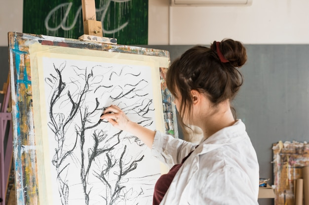 Woman drawing with charcoal on canvas at workshop
