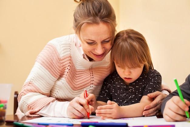 Женщина рисует с девушкой с синдромом дауна