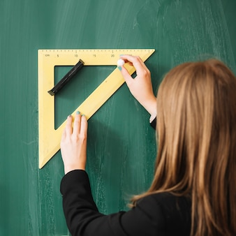 Woman drawing with triangular ruler on blackboard
