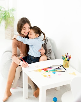 Woman drawing with young girl at desk