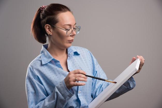 여자는 회색에 브러시로 캔버스에 무언가를 그립니다.