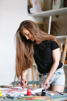 Woman draws watermelon slices on a white t-shirt