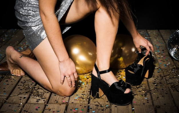 Woman in dress attiring shoes near ornament balls