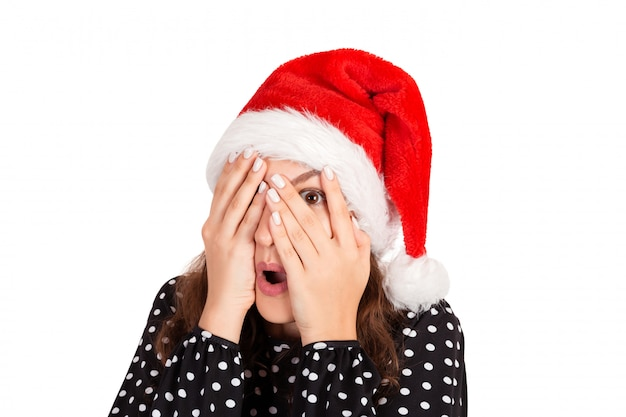 Woman in dress feeling scared but curious with one eye peeking through fingers. emotional girl in santa claus christmas hat isolated on white background. holiday