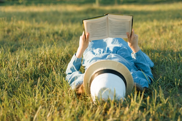 Woman in dress and hat on green grass reading book