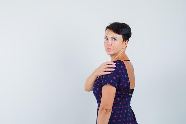 Donna in vestito che osserva sopra la sua spalla e che sembra interessata.