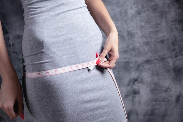 Woman in dress measures her waist