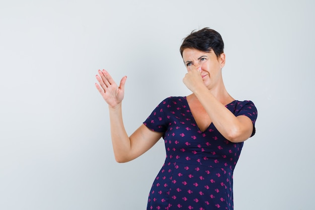 Woman in dress pinching her nose due to bad smell and looking disgusted