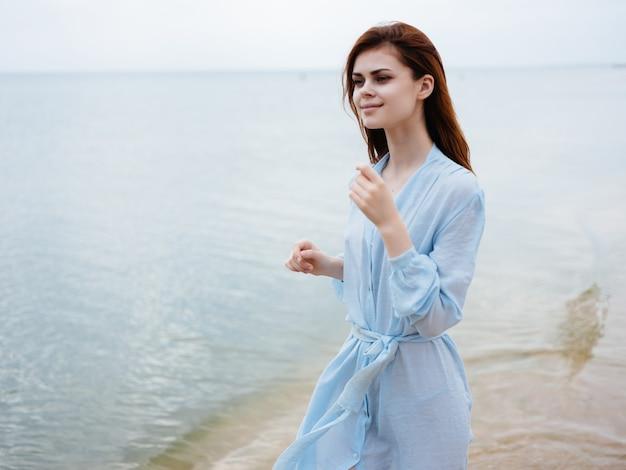 Woman in dress red hair beach ocean fresh air leisure