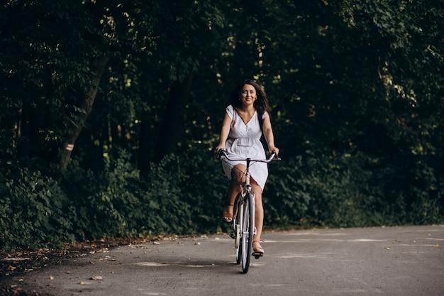Donna in vestito che guida la bicicletta nel parco