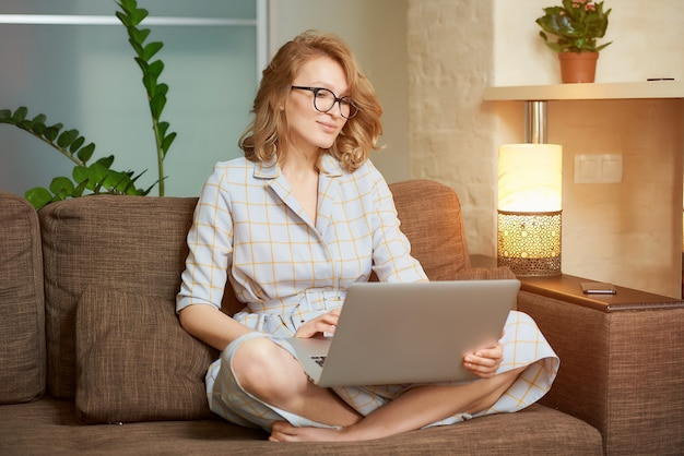 A woman in a dress sitting on the couch with legs crossed works remotely on a laptop. a happy girl watching a webinar in her apartment.