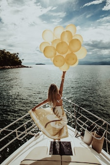 Woman in a dress standing on a yacht, holding golden balloons while sailing