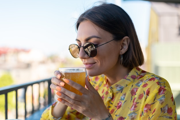 Woman in dress in summer cafe enjoying cool kombucha glass of beer sniffing smell with eyes closed