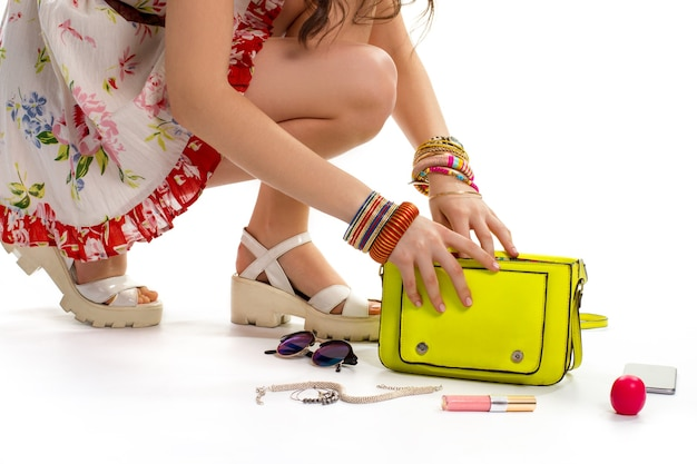 Woman in dress touches bag. lipstick near lime purse. bijouterie and cosmetics. brand new accessories.
