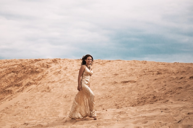 Woman in dress walking in the sand of desert dunes with steps in the desert sand, young woman walking in white sand on a bright summer day