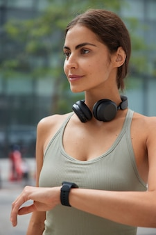 Woman dressed in activewear checks results of fitness training wears wireless headphones around neck poses on blurred