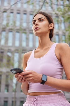 Woman dressed in activewear uses mobile phone for finding route strolls in city focused into distance enjoys sport activities going to have cardio training