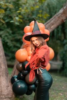 ハロウィーンの魔女に扮した女性。森の背景にオレンジ色のボール。ハロウィーン
