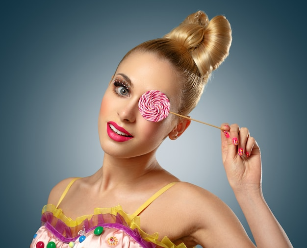 Woman dressed as a doll with lollipop.