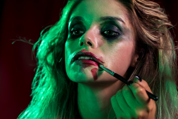 Woman dressed as joker using a brush