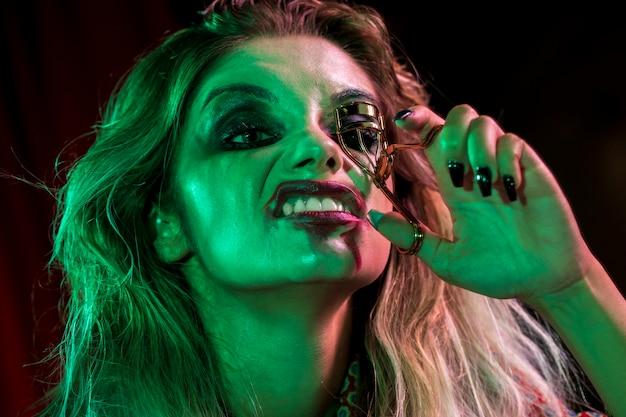 Woman dressed as joker using a eyelash curler