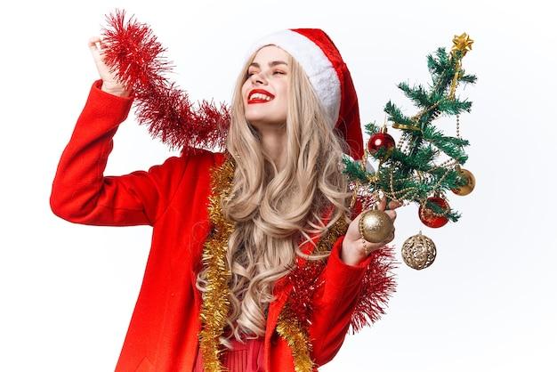 サンタのクリスマスツリーの装飾の休日の喜びに扮した女性