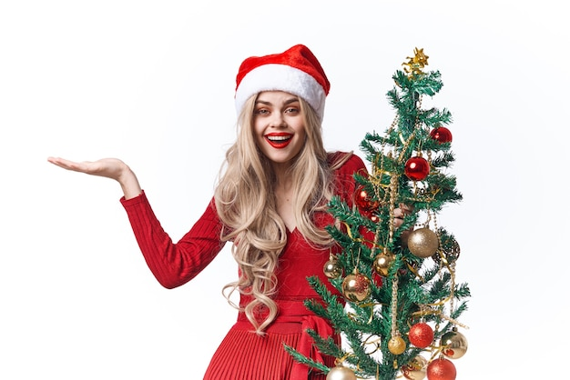サンタのクリスマスツリーの伝統の休日の明るい背景に扮した女性
