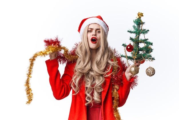 木の贈り物の休日を飾るサンタクロースに扮した女性