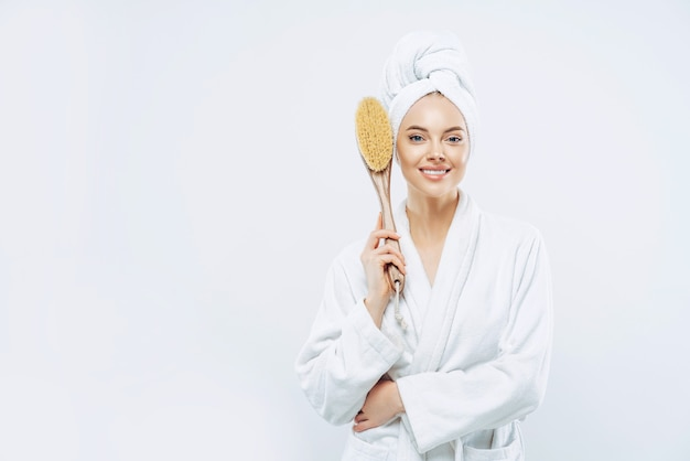 Woman dressed in bath robe holds anticellulite massage brush