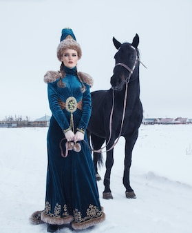 Woman dressed in beautiful dress in winter landscape with horse