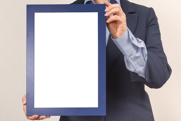 Woman dressed in a business suit holds a mockup of a frame picture