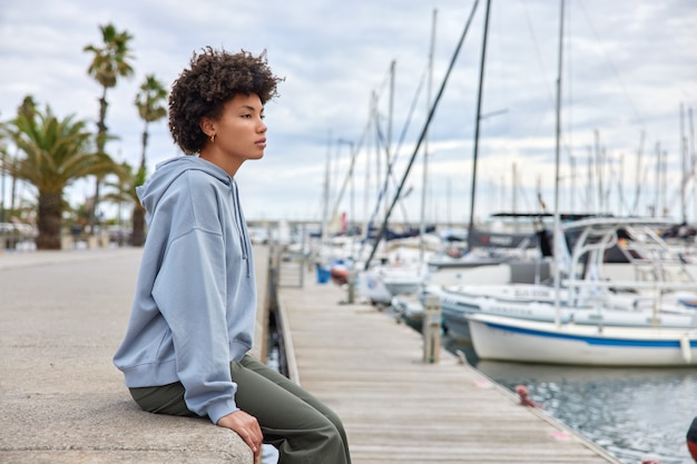 Woman dressed in casual clothes admires view near sea port breathes marine air focused into distance