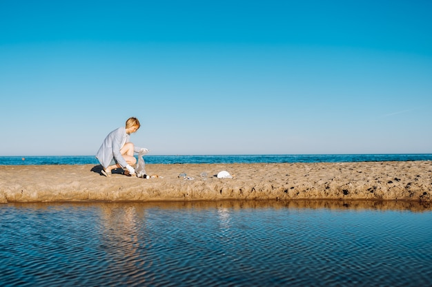 Woman dressed in casual clothes collects garbage on the beach on a summer sunny day