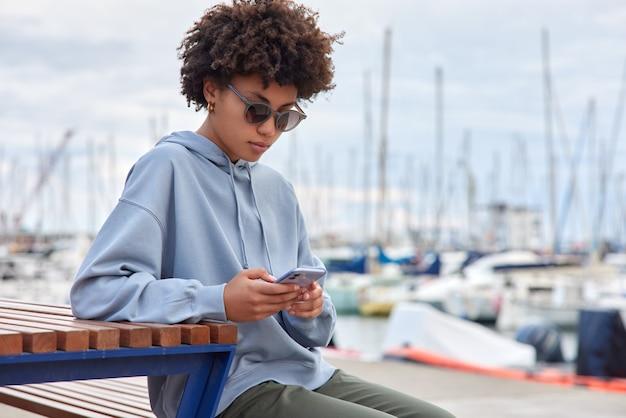 Donna vestita con felpa con cappuccio casual occhiali da sole alla moda utilizza le notifiche dei controlli dello smartphone si siede su una panca di legno vicino al porto ammira la vista di navi e yacht