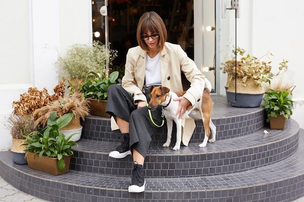 Женщина в небрежно одетой одежде сидит на лестнице и держит собаку на поводке