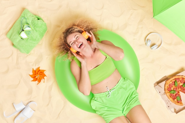 La donna vestita con top corto e pantaloncini si diverte ad ascoltare musica tramite le cuffie pone sulla spiaggia sabbiosa da sola mangia la pizza si trova sul costume da bagno gonfiato verde.