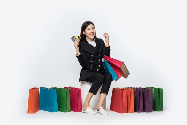 The woman dressed in dark went shopping, carrying credit cards and lots of bags