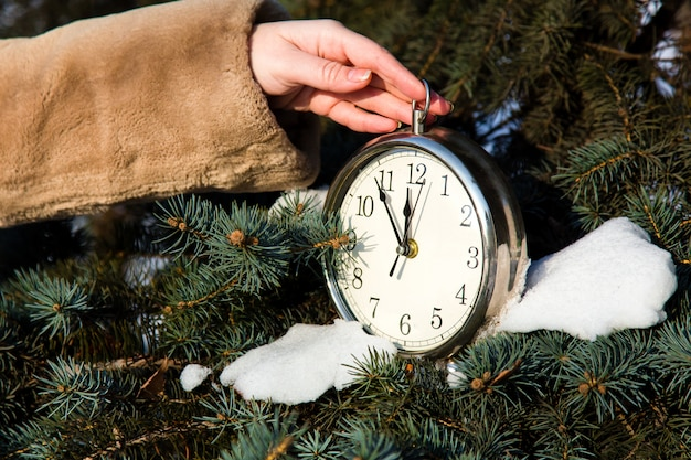 Woman dressed in a fur coat hanging a watch on fir closeup.
