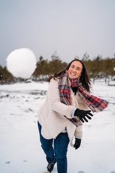 Женщина, одетая в пальто, улыбается, потому что она бросила снежок в камеру. концепция отпуска