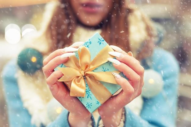 降雪のある通りでシルクリボンのギフトボックスを保持している暖かい青いコートを着た女性