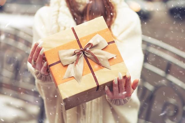 雪の降る通りでシルクの弓で大きなギフトボックスを保持している白いコートを着た女性