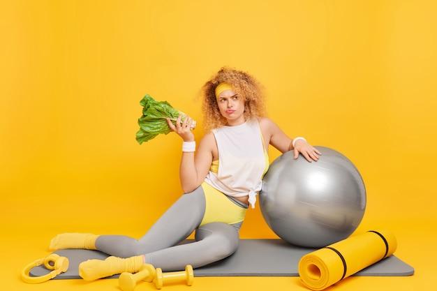 Женщина, одетая в спортивную одежду, придерживается диеты, держит позы зеленых овощей на коврике со спортивным инвентарем