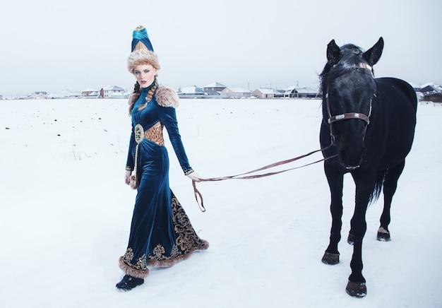 馬のある冬景色の美しいドレスに身を包んだ女性