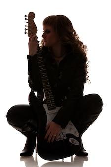 여자는 검은 가죽 옷을 입고 쪼그리고 앉고 기타를 움켜 쥐고 있습니다. 머리를 옆으로 돌렸다