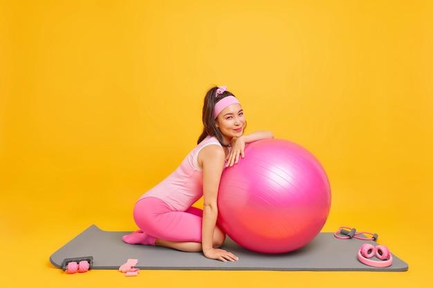 Женщина, одетая в боди, позирует на коврике для йоги с фитнес-мячом, использует эластичную ленту и различное спортивное оборудование, изолированное на желтом